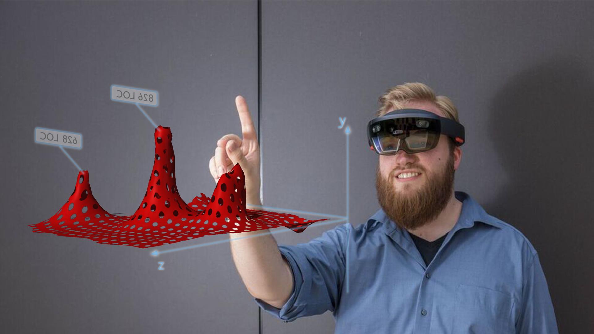 Ein Mann trägt eine VR Brille und zeigt mit dem Finger auf eine Grafik, die im Raum vor ihm erscheint.