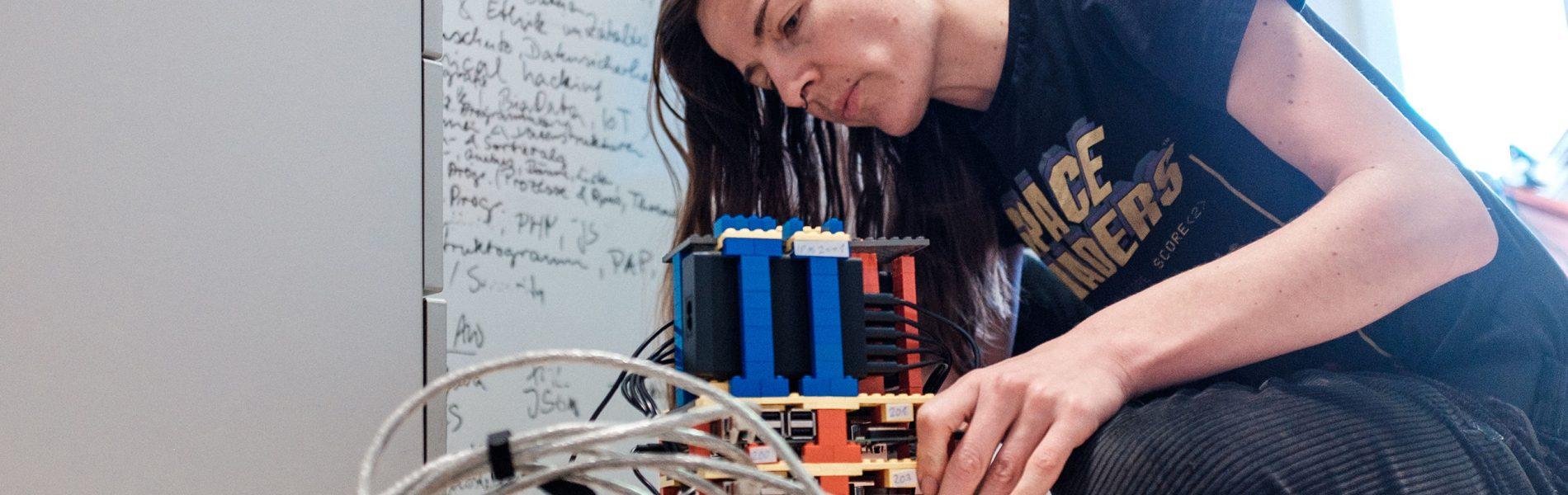 Das Bild zeigt eine Person, die an einem größeren Gebilde aus LEGO-Steinen arbeitet. Es sind viele Ports im Gebilde zu erkennen.