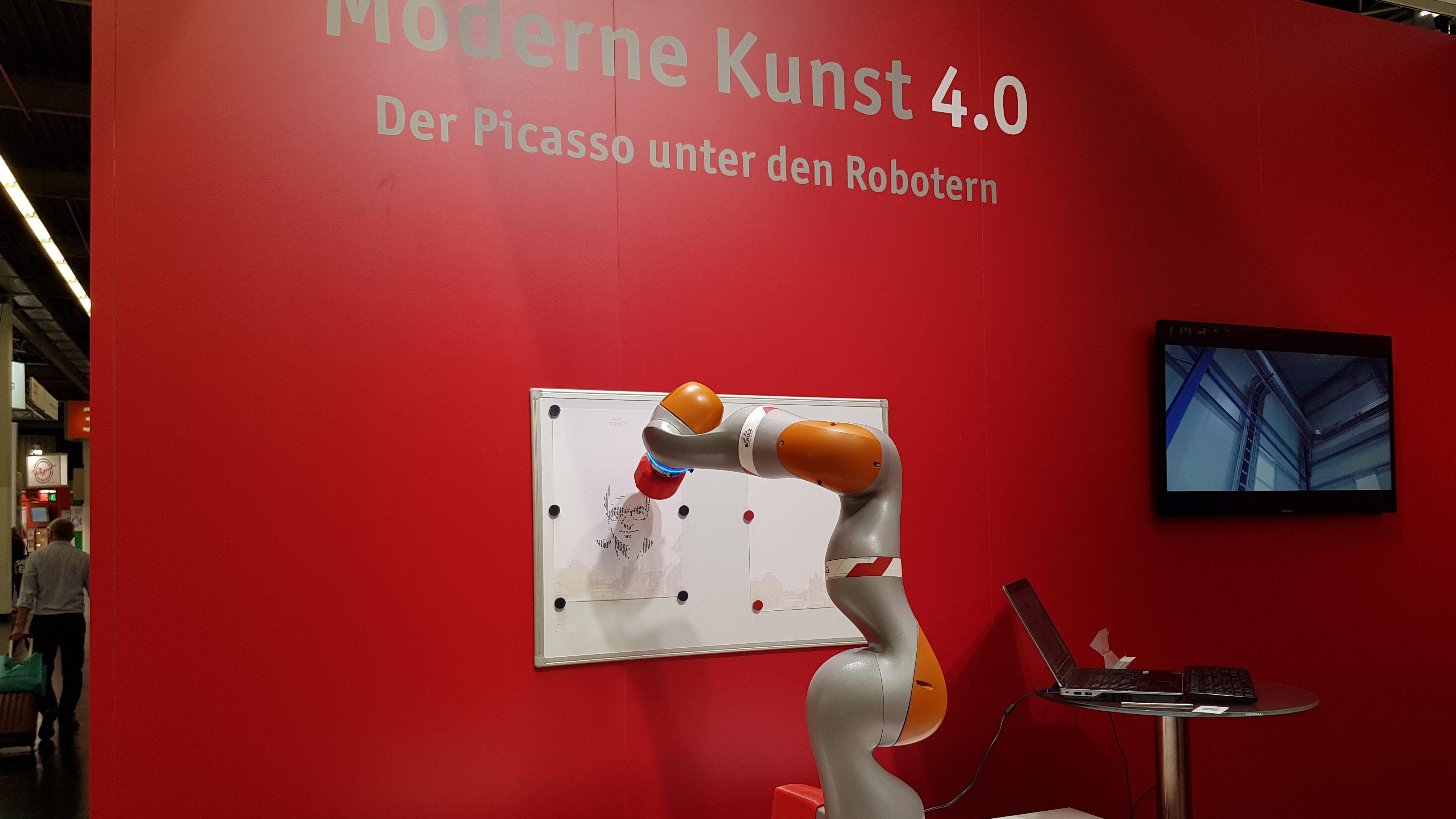 Auf dem Bild sieht man einen Roboterarm, der ein Gesicht zeichnet.