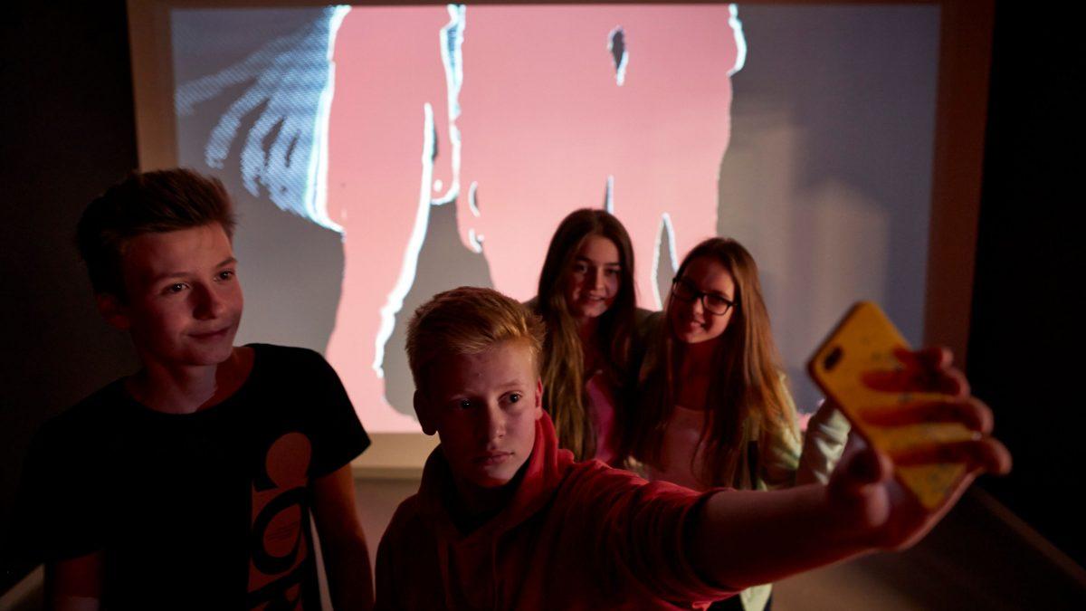 Mehrere junge Leute machen ein Selfie in einem dunklen Raum. Ihre Schatten werden auf einen Bildschirm projiziert.