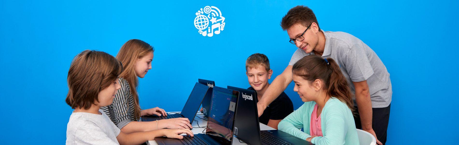 Vier Kinder sitzen vor Laptops und ein junger Mann schaut dabei zu. Der Hintergrund ist leuchtend blau.