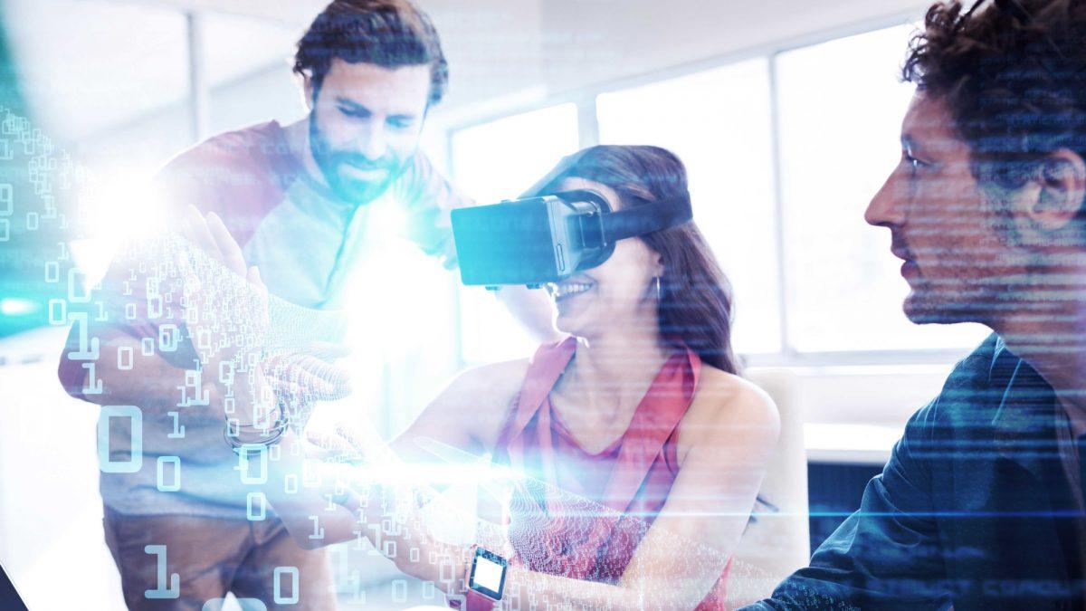 Das Bild zeigt drei Personen. Die mittlere Person trägt eine Virtual Reality Brille. Durch Einsen und Nullen, die durchs Bild schweben, soll das Gefühl von virtueller Realität übermittelt werden.
