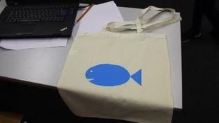 Dieses Bild zeigt einen Jutebeutel mit einem Aufdruck, der einen blauen Fisch darstellt.