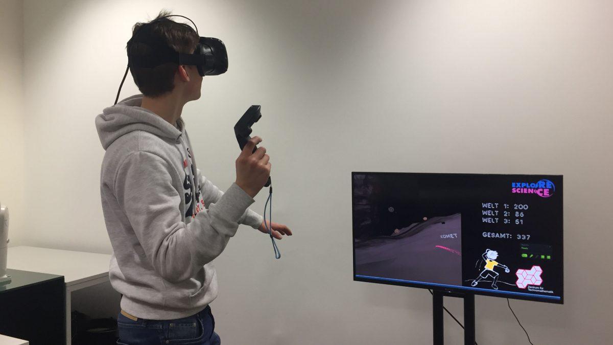 Ein Mann trägt eine Virtual Reality Brille und hat einen Controller in der Hand. Er spielt offensichtlich ein Spiel, wie man auf dem Bildschirm vor ihm sehen kann.