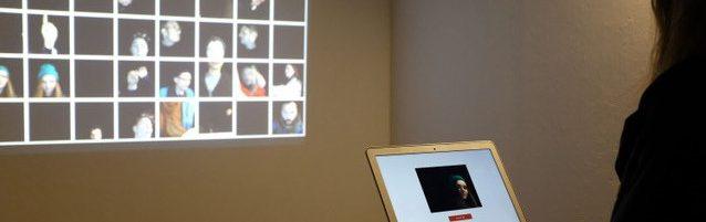 Eine Person steht in einem abgedunkelten Raum vor einem Laptop und sieht sich projizierte Bilder an der Wand dahinter an.