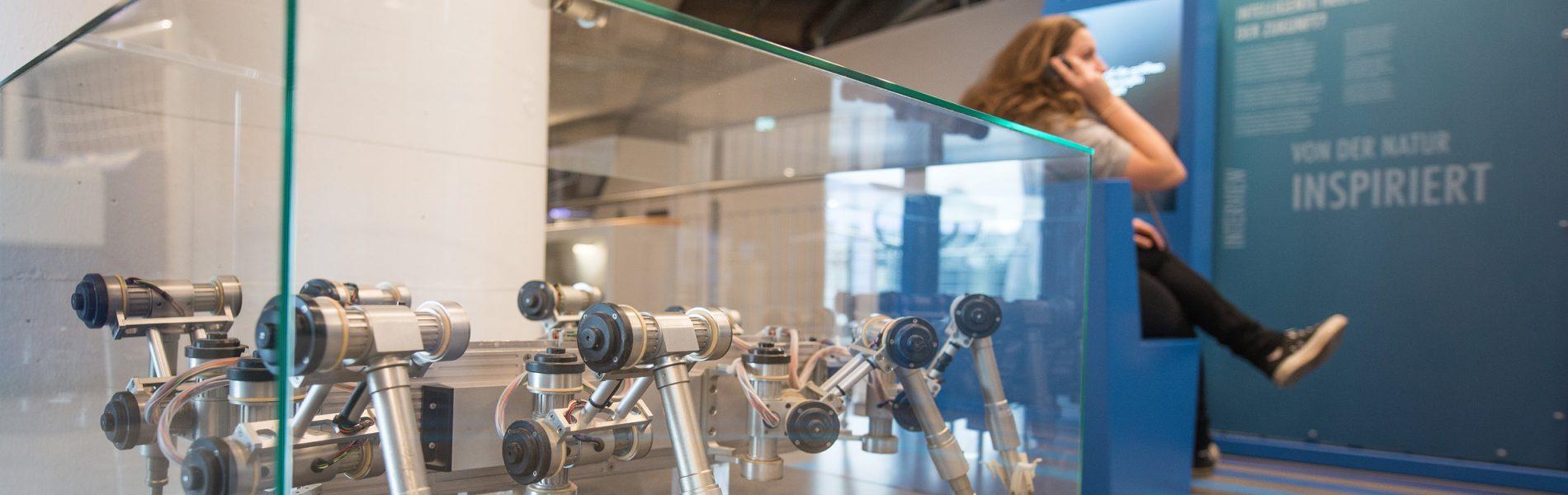 Dieses Bild zeigt einen Roboter in einer Vitrine. Er hat acht Beine und einen länglichen Körper.