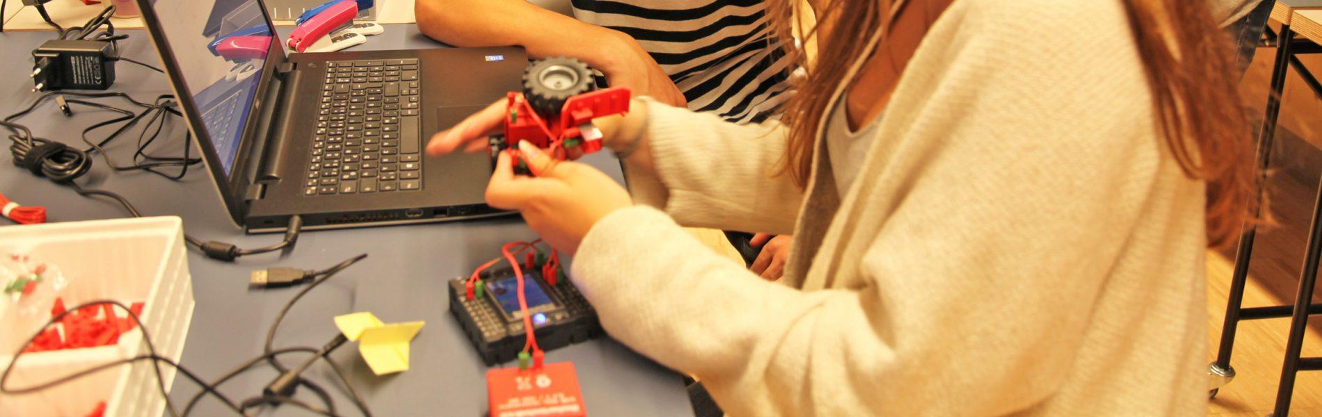Mehrere Personen sitzen vor einem Laptop und bauen einen Roboter zusammen.