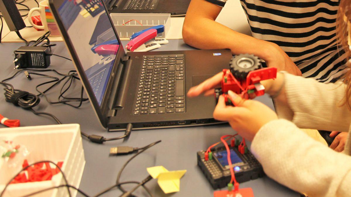 Zwei Personen sitzen vor einem Laptop und bauen einen Roboter zusammen.