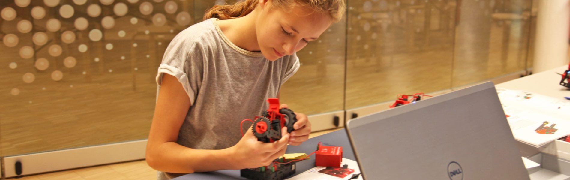 Ein Mädchen baut einen Roboter zusammen.
