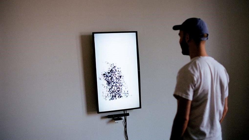 Auf diesem Bild sieht man einen Mann, der vor einem Bildschirm im Hochformat steht.
