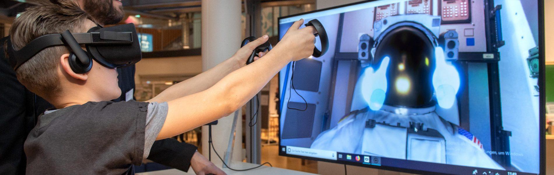 Auf diesem Bild sieht man einen Jungen, der mit einer Virtual Reality Brille und zwei Controllern in den Händen vor einem Bildschirm steht.